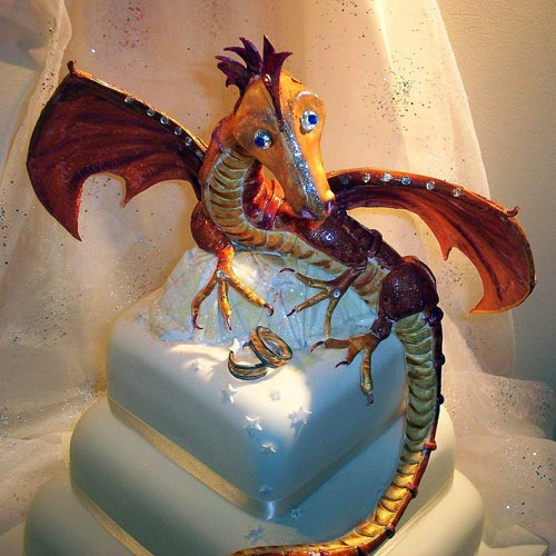 Three tier white fondant wedding cake, with an amazing orange and red dragon wedding cake topper and bride and groom ring set
