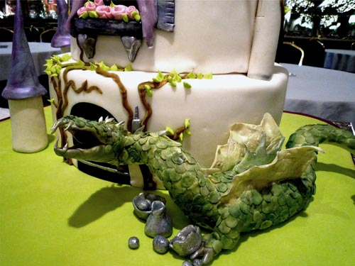 Hand painted castle wedding cake, decorated with an intricately designed green dragon with scales and wings