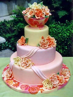 Three tier round pastel pink, yellow and apricot fondant wedding cake. Decorated with fancy handmade orange, yellow and pink sugar paste flowers