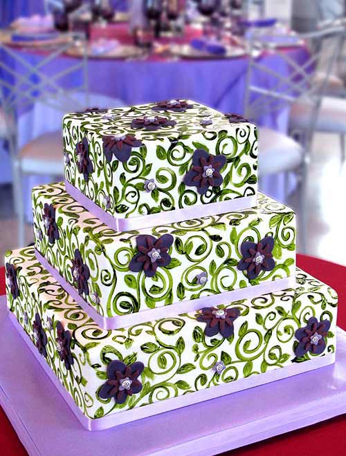 Fancy square three tier white, purple and green wedding cake decorated with lilac ribbon, green scrolls and patterns and lovely hand crafted purple fondant flowers