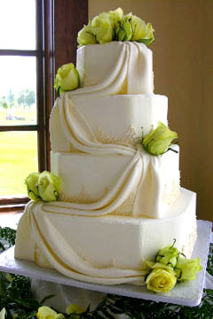 Four tier ivory wedding cake decorated with yellow roses