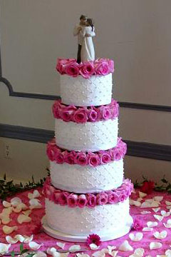 Four tier white and pink wedding cake garnished with pink roses