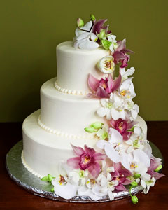 Three tier white wedding cake  decorated with cascading fresh orchids