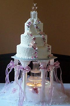 Three tier pink and white castle wedding cake raised up on 5 pillars to allow a wedding cake fountain underneath