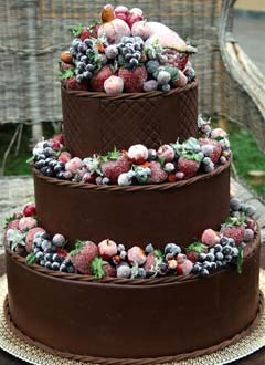 three tier, rich chocolate wedding cake decorated with fresh berry fruits