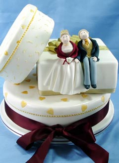 Three tier white novelty wedding cake with caricatures of both the bride and groom