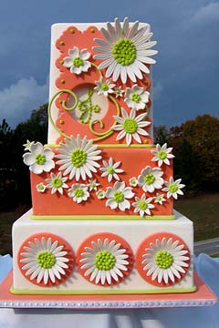 Three tier white and orange 1960's style wedding cake