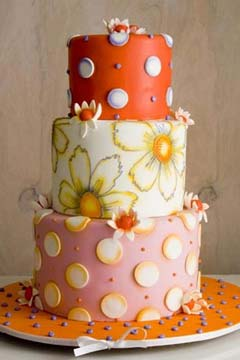 Three tier pink, white, orange and yellow 1960's inspired wedding cake. Decorated with polka dots and flowers