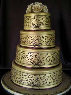 Round four tier gold and brown wedding cake decorated with ornated patterns and scroll work