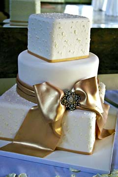 Square and round three tier gold and ivory wedding cake decorated with a huge hand made gold fondant ribbon and bow