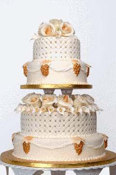 Unusual four tier honey gold and white wedding cake, set up on two different platforms