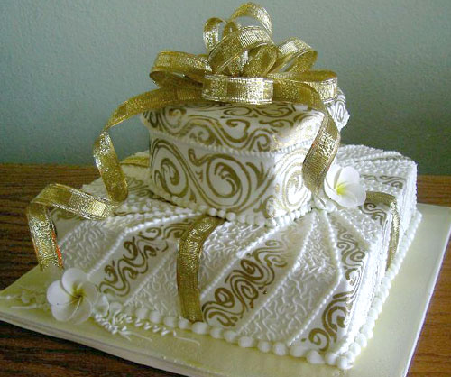 Two tier gold and white wedding cake with gold ribbon arranged as a wedding cake topper