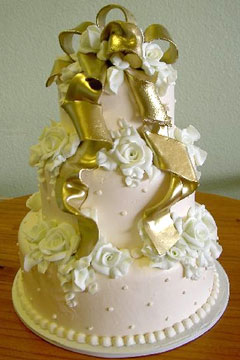 three tier gold and white wedding cake is round and decorated with white gumpaste roses