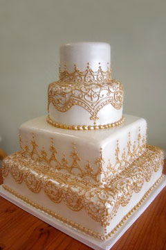 four tier white and honey gold cake is square on the bottom half and the two top tiers are round