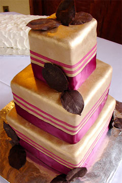 Three tier square wedding cake has fuchsia pink and honey gold cake icing