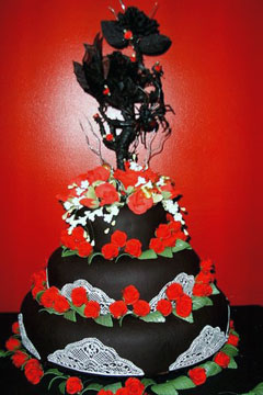 Gorgeous three tier blakc and white Goth style wedding cake, decorated with black sugar paste roses and thorns