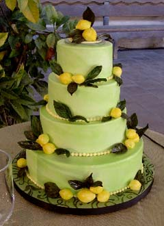 Round four tier green and yellow wedding cake decorated with hand made fondant lemons