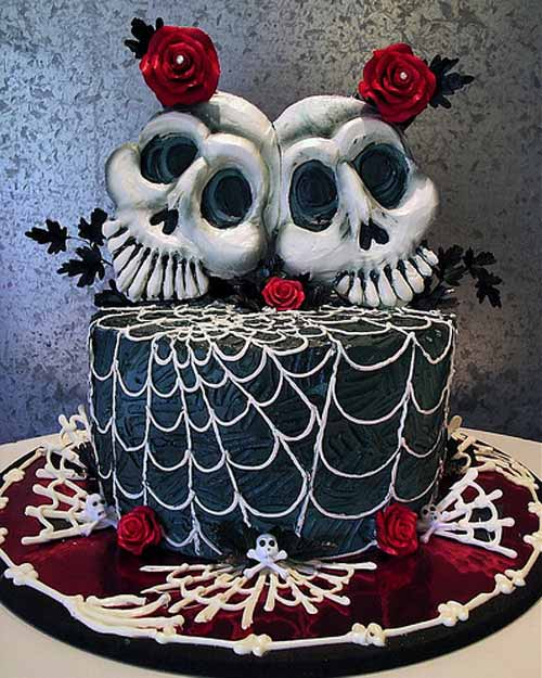 spooky black halloween wedding cake with two skulls as the bride and groom wedding cake topper decorated with spider webs and rich red roses