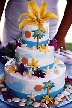 Three tier Hawaii Maui theme wedding cake garnished with tropical pine trees and seashells