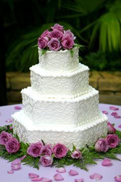 Four Tier Hexagon Shaped Buttercream Wedding Cake Decorated With White Scroll Work And Pink Roses