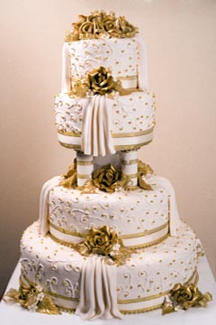 A Large Four Tier White And Gold Ethnic Wedding Cake Made With Buttercream Icing Covered Over Fondant Frosting Then Decorated
