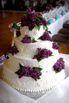 Very Elegant Four Tier Buttercream Wedding Cake Decorated Buttercream Icing  Swirls And Purple Flowers.