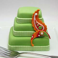 Retro three tier mini green wedding cake embellished with a vibrant orange