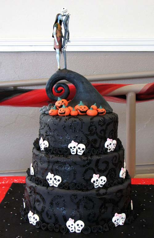three tier black wedding cake with a nightmare before christmas wedding cake decorated with black patterns and swirls white scull heads and organge