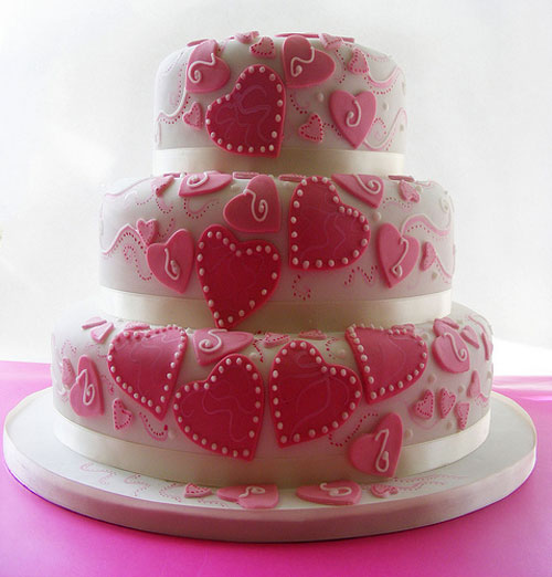 Groovy three tier wedding cake design, decorated with pink hearts and white satin ribbon