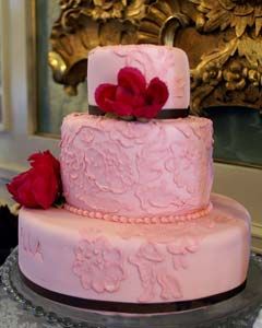 Pink three tier brocade wedding cake, decorated with floral patterns and red flowers