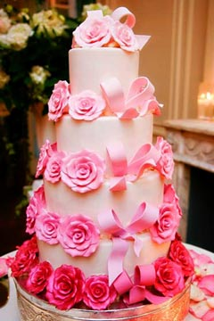 Four tier wedding cake decorated with pastel pink and fuchsia handmade fondant roses and bows