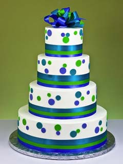 Four tier white wedding cake with blue and green polka dots
