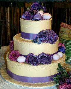 Romantic three tier round purple and cream wedding cake decorated with purple ribbon