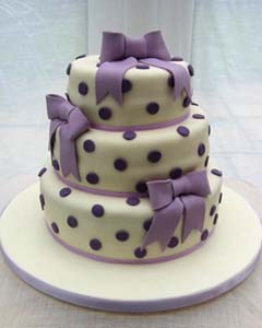 Round three tier white and purple polka dot wedding cake