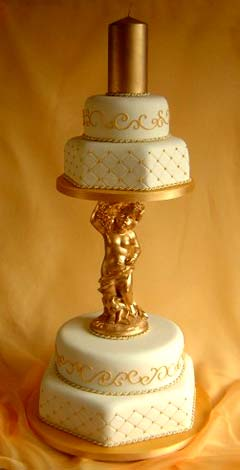Vintage, four tier white and gold cherub wedding cake decorated with gold pin cushion patterns and golden swirls