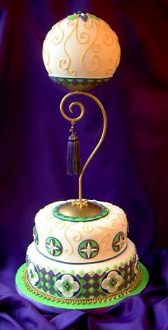 Three tier white, green and purple vintage wedding cake with art deco patterns and gold swirl motif with a vintage ball cake topper