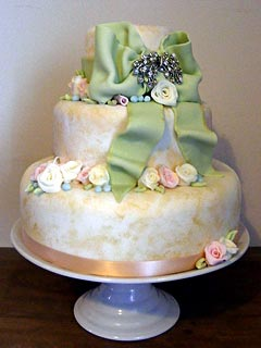 Three tier romantic Victorian style, shabby chic wedding cake with intricate lacework on the fondant