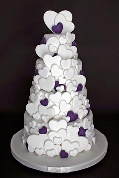 four tier white and purple wedding cake decorated with lots of white and purple edible heart shaped sugar paste hearts