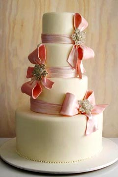 romantic four tier pink and ivory wedding cake decorated with hand crafted pink fondant and large pink fondant bows