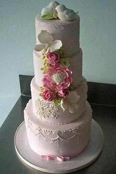 four tier pastel pink wedding cake, decorated with ornate and intricate patterns, handmade sugar and fondant flowers