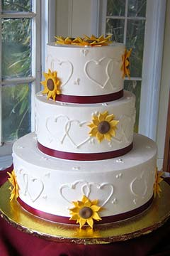 Three tier round white wedding cake decorated with yellow sunflowers