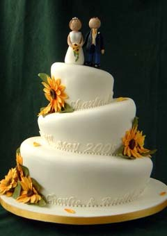 Three tier topsy turvy wedding cake decorated with orange sunflowers