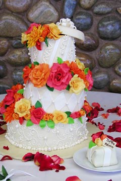 Small Whimsical Three Tier White Wedding Cake Decorated With Squiggles Scrolls And Diamond Shapes Then Embellished Yellow Orange Pink