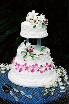 Three tier white buttercream wedding cake decorated with pink flowers and white lillies