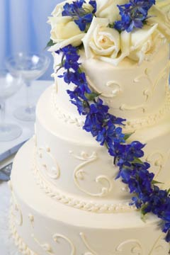 Three tier white wedding cake decorated with blue tropical flowers