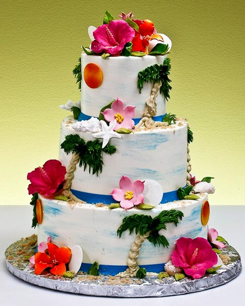 Three tier white and blue Hawiian wedding cake decorated with hand painted palm trees, sea shells and an air brushed blue sky
