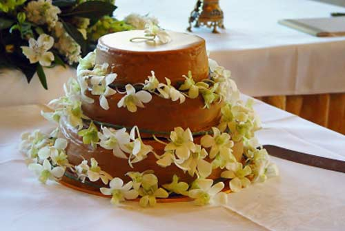Unusual three tier cake, decorated with fresh white and green orchid flowers. Looks just like a large cream caramel