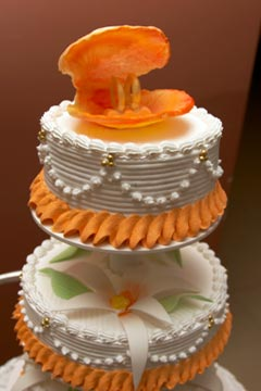 Two tier orange and white buttercream wedding cake, with an orange oyster shell with wedding bands inside