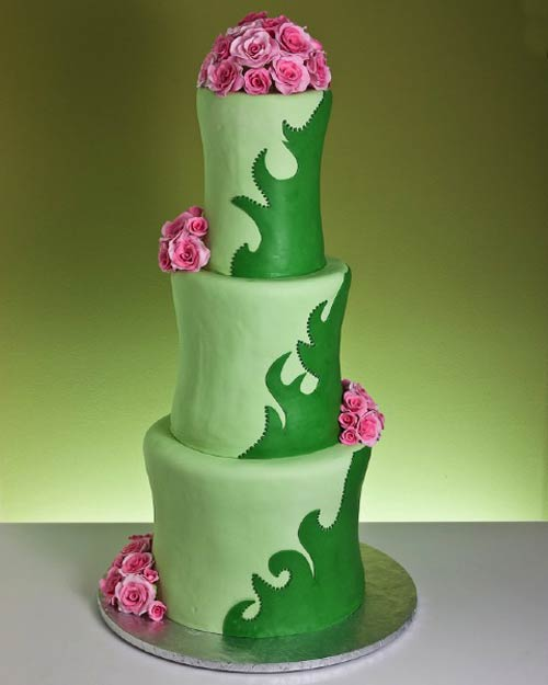 Three tier, contemporary style, tall two tone green wedding cake with green swirls. Decorated with fresh pink roses
