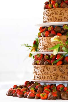 three tier chocolate strawberries wedding cake placed on platforms layers. Each tier is decorated with chocolate dipped strawberries